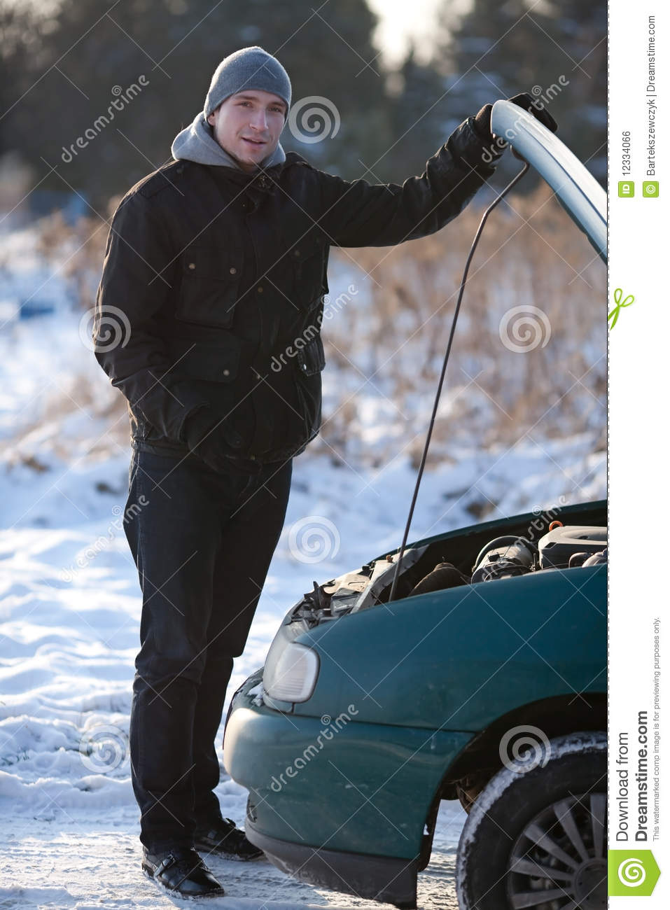 Young Man In Snow With Broken Down Car Stock Photography