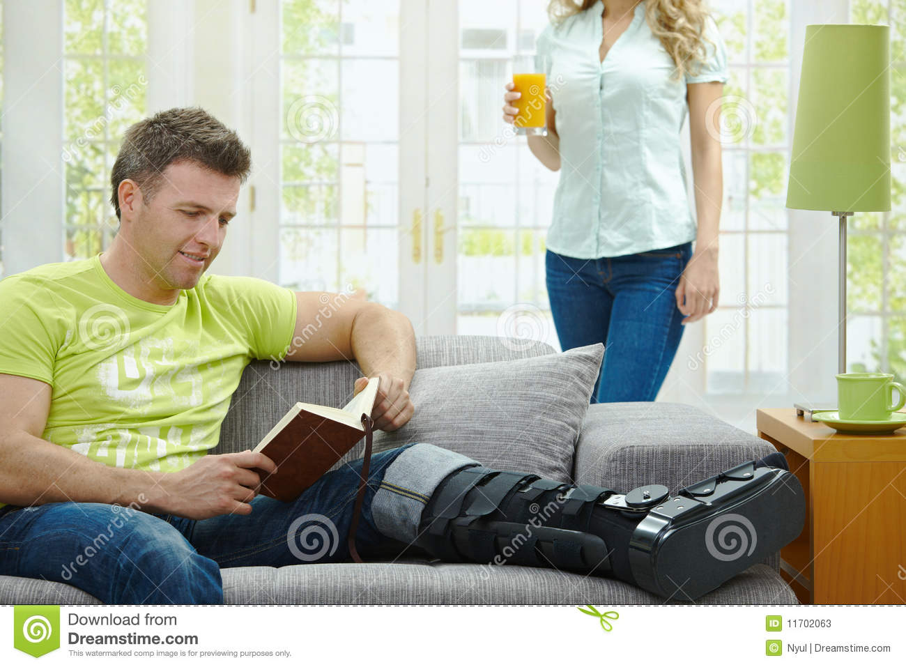 Man Rasting His Broken Leg In Cast On Sofa At Home Reading Book