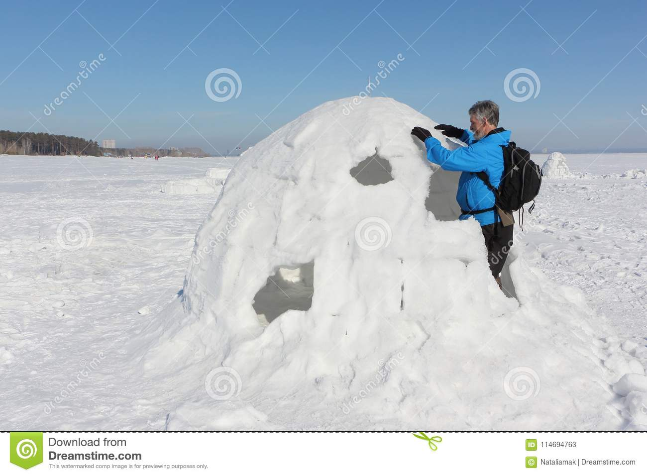 Man building an igloo in winter