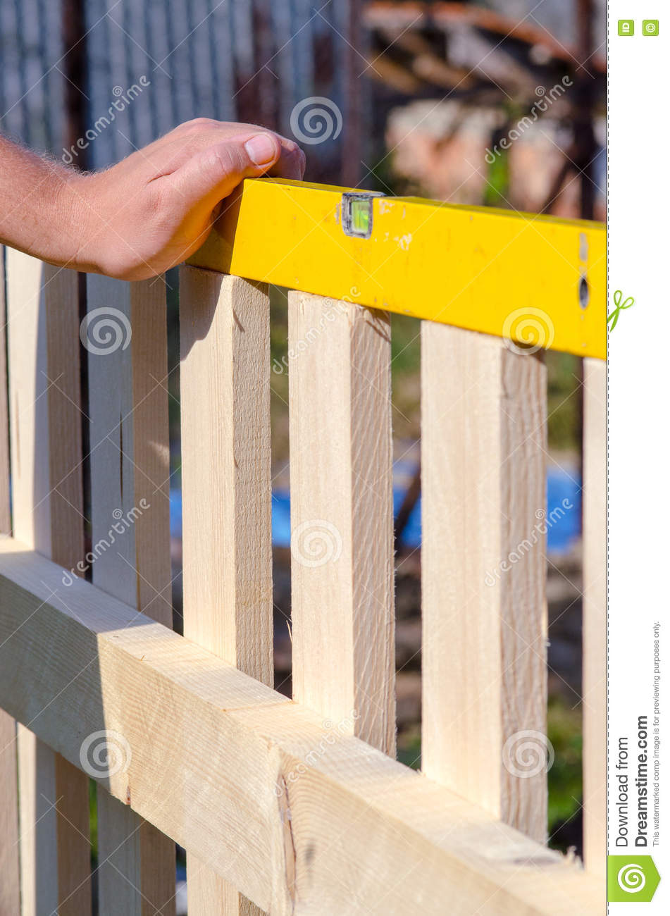 Man building a wooden fence and checking with spirit level. Close up of his hand and the tool in a DIY concept.