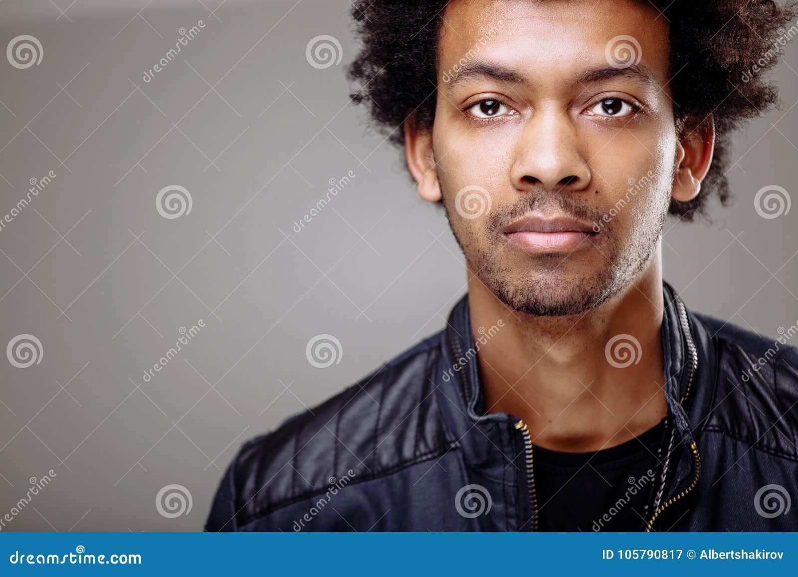 Man With Bushy Curly Hair Blinking His Eye Having Warm Broad Smile