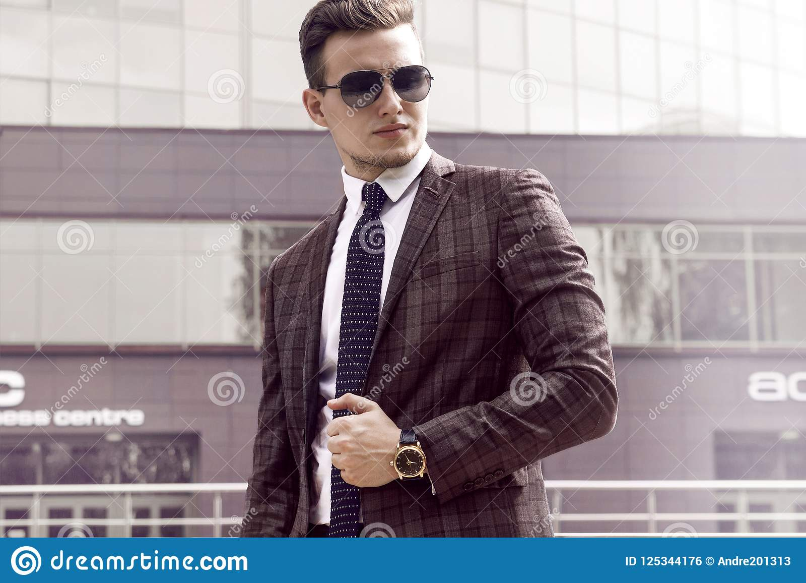 Man businessman in sunglasses jacket and tie against the background of urban landscape