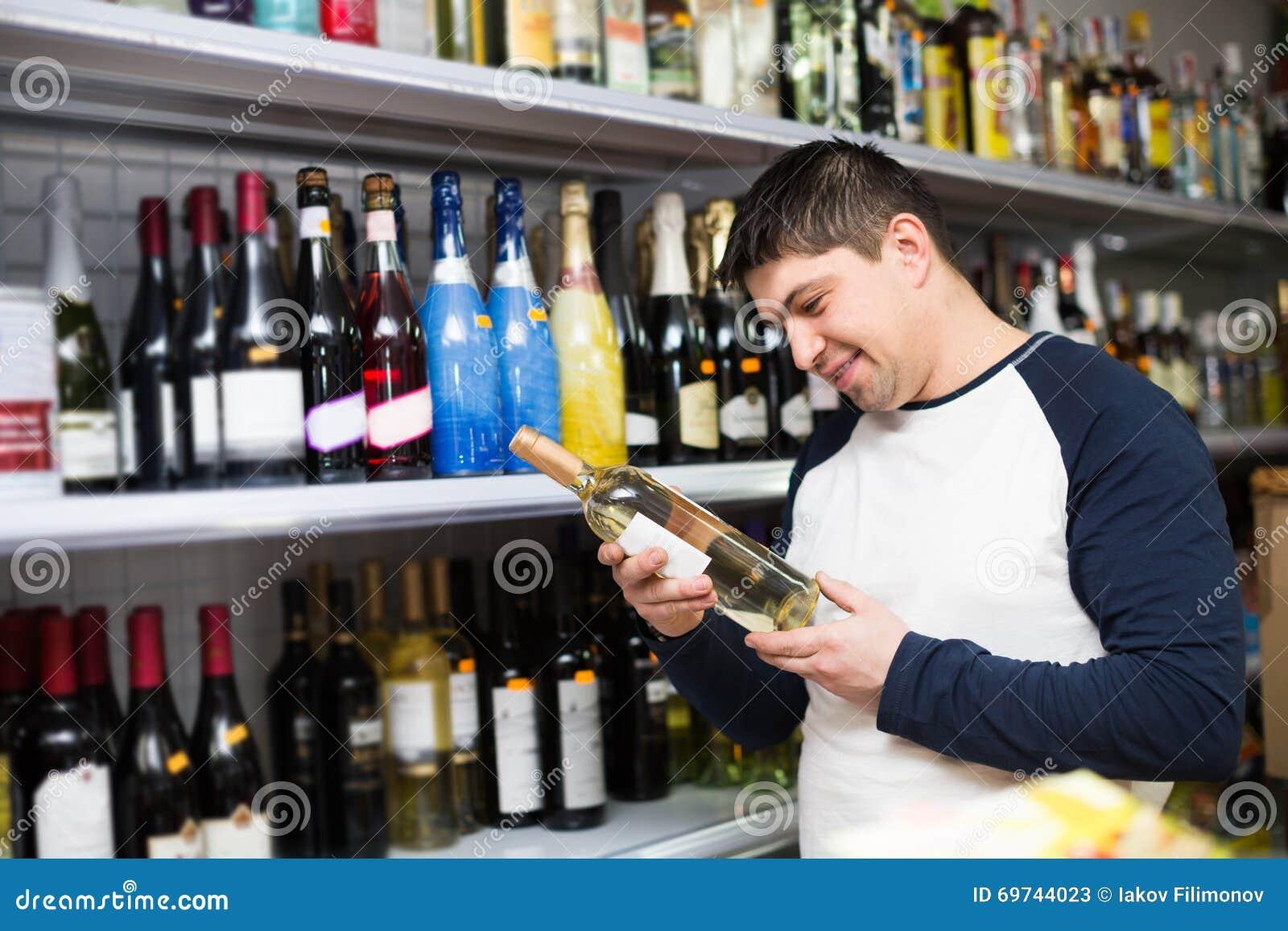Man Buying Bottle Of Wine Stock Photo - Image: 69744023