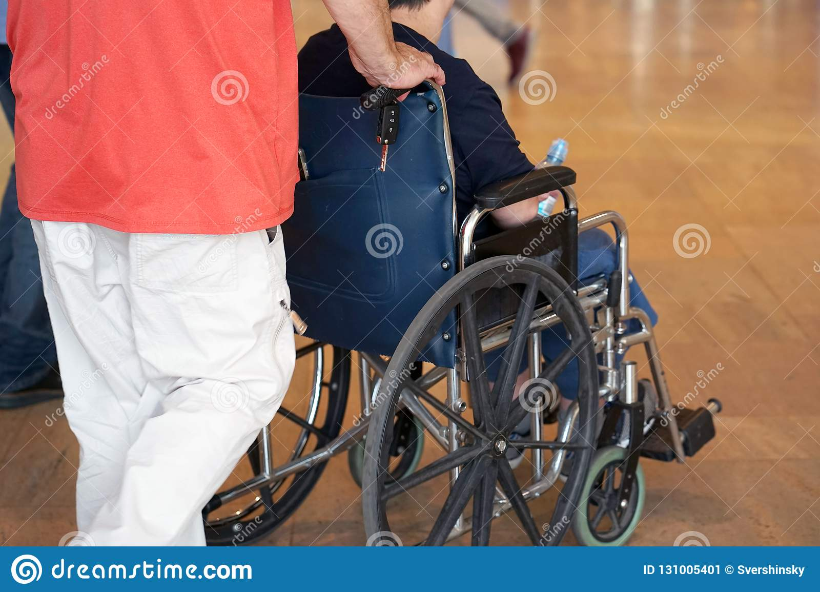 The man carries a disabled person in a wheelchair