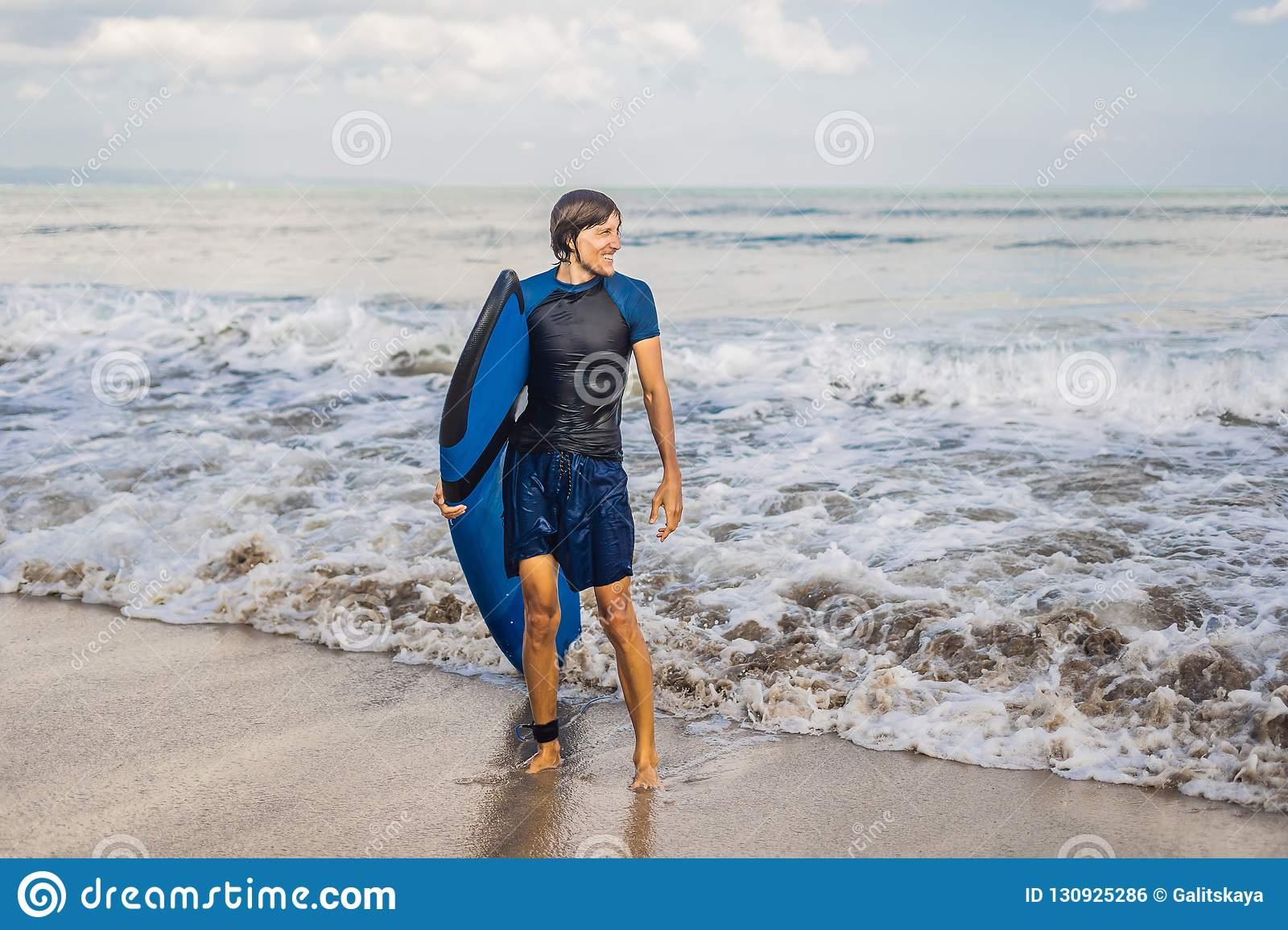 Man carrying surfboard over his head. Close up of handsome guy w