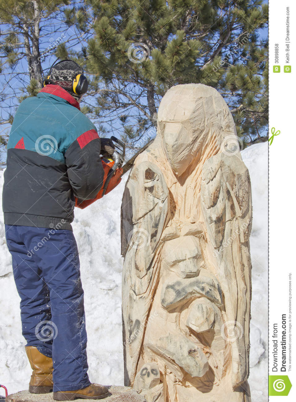 Man carving details of huge bear from log with chainsaw
