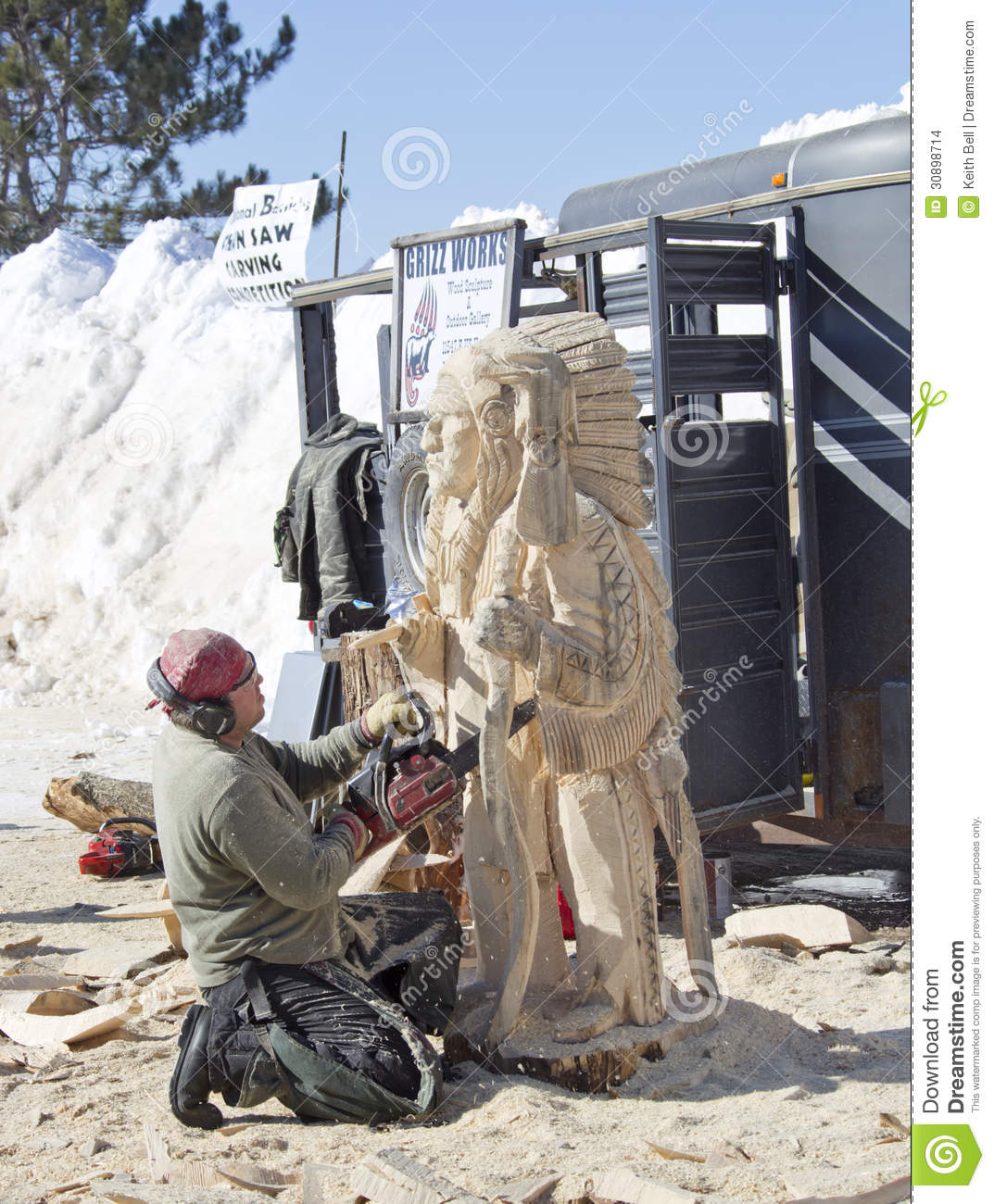 Man carving indian chief with chainsaw editorial stock