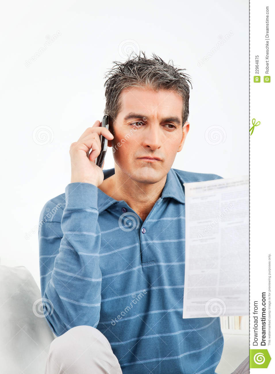 Man On Cell Phone : Man with cell phone and bill stock image