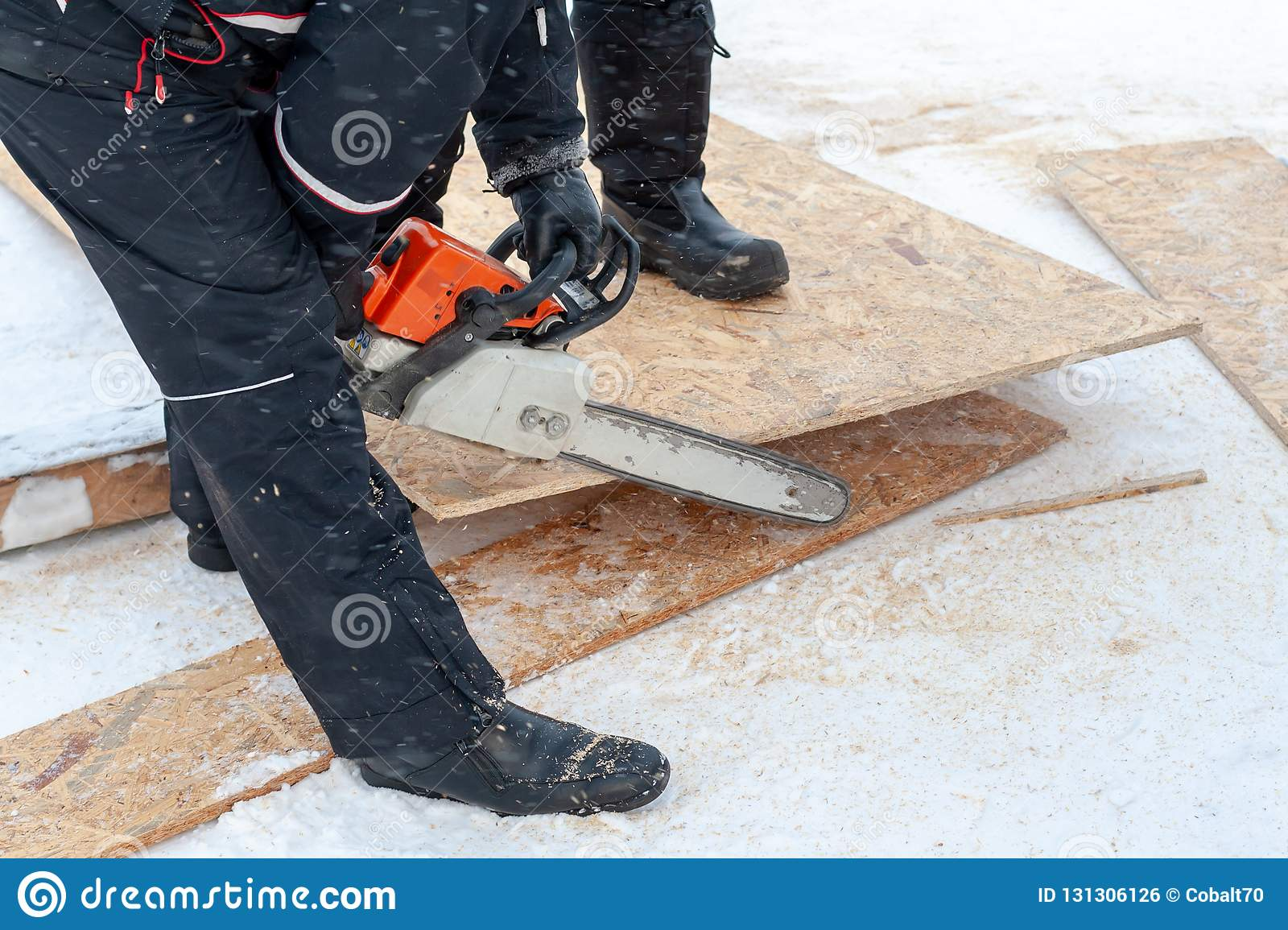 A man chainsaw sawing a wooden panel on a winter day on a background of snow