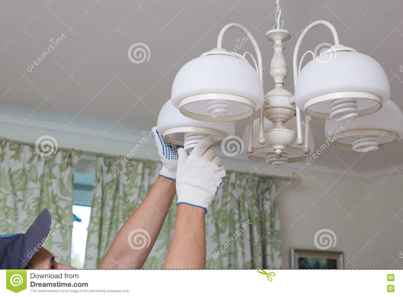 Man changes an electric light bulb, energy efficiency