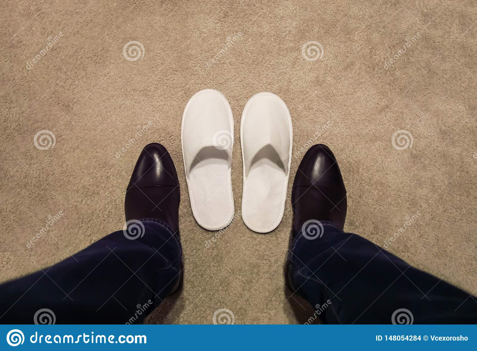 A man changes his shoes, takes off his shoes, he wears white slippers