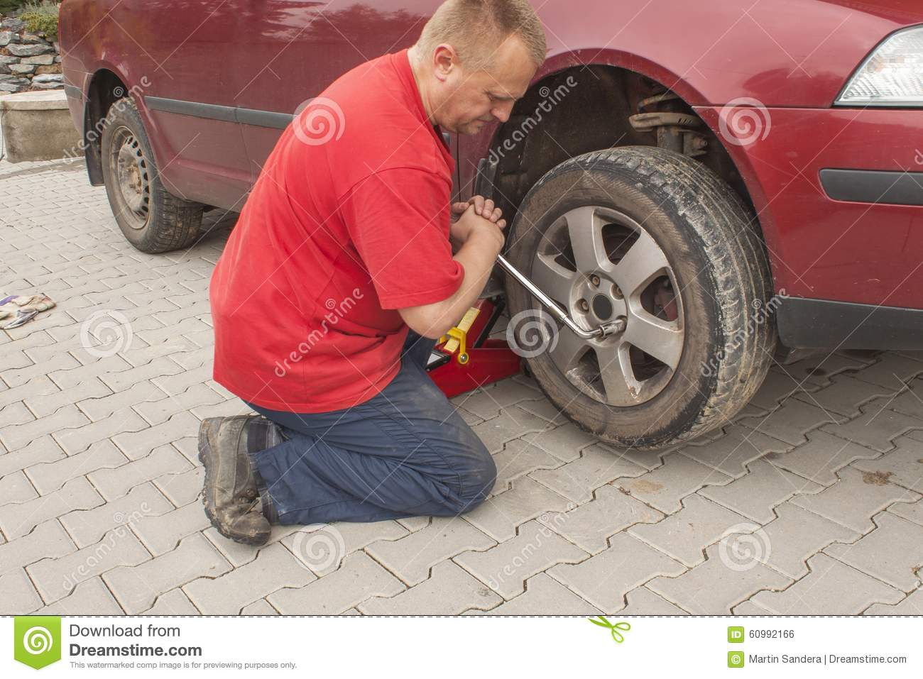man changing the punctured tyre on his car loosening the nuts with a wheel spanner before. Black Bedroom Furniture Sets. Home Design Ideas