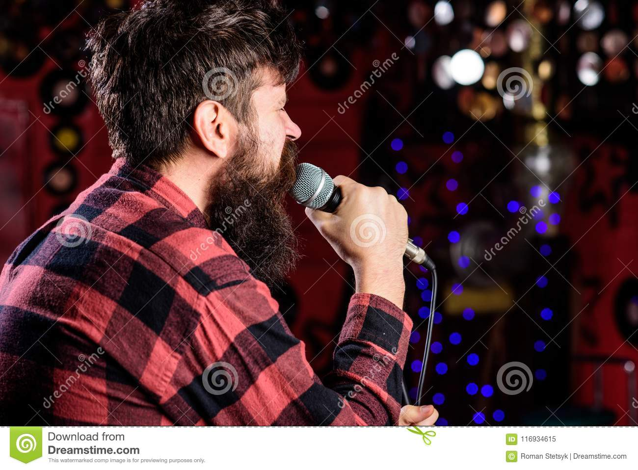 21ff0829491 Man In Checkered Shirt Holds Microphone