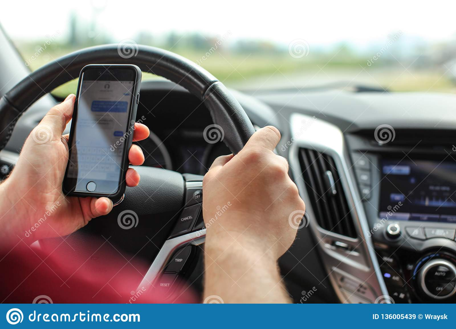 Man checking his text messages while driving. Dangerous texting in car concept