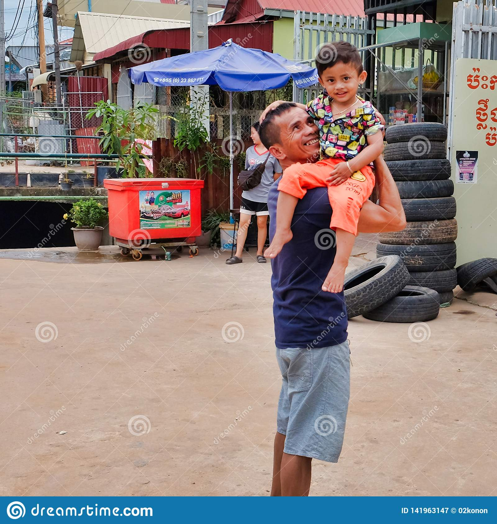 Man with a child in his arms near the tire shop, slums of Asia, residents of poor areas of the