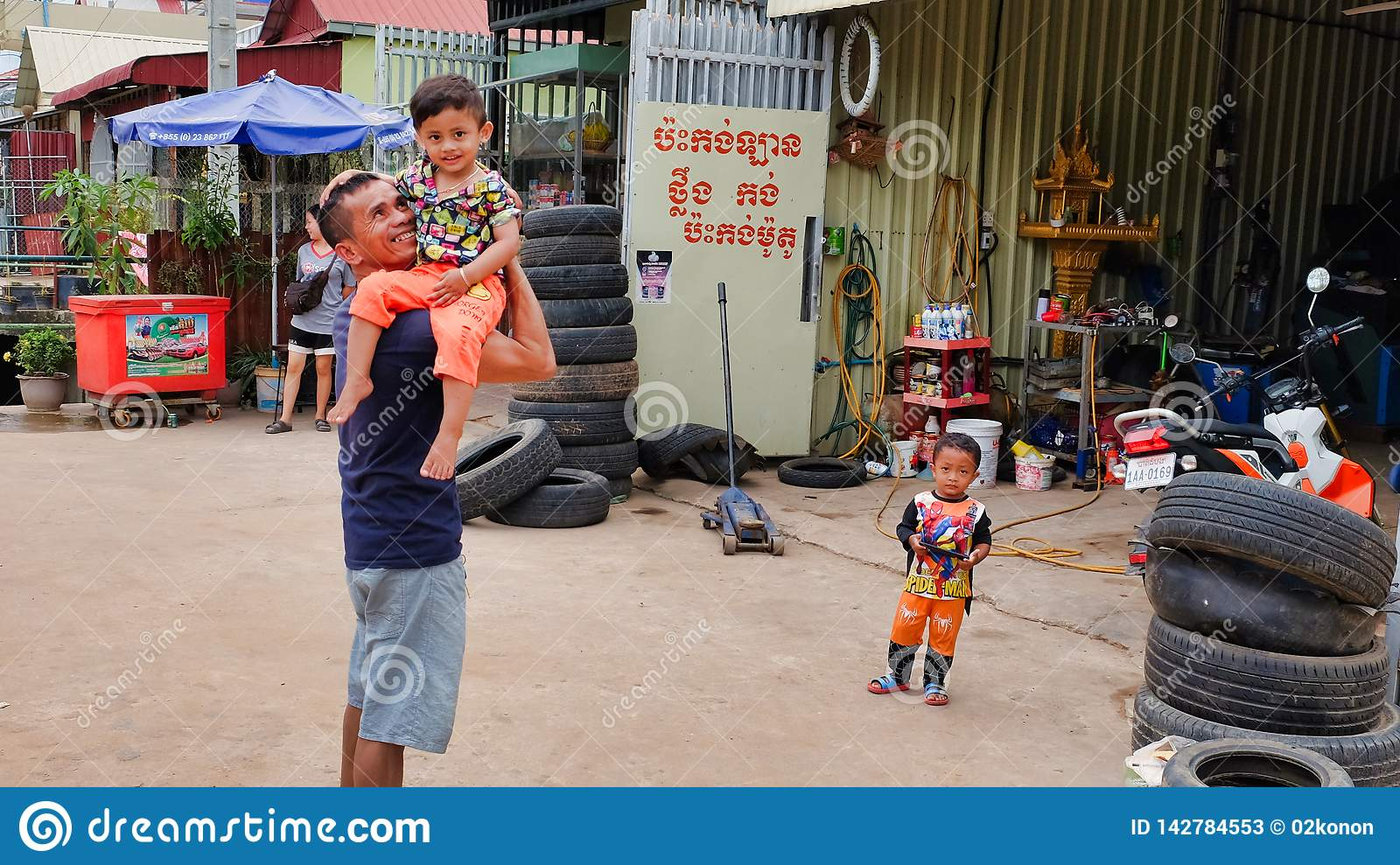 A man with a child in his arms near the tire shop, slums of Asia, residents of poor areas of the