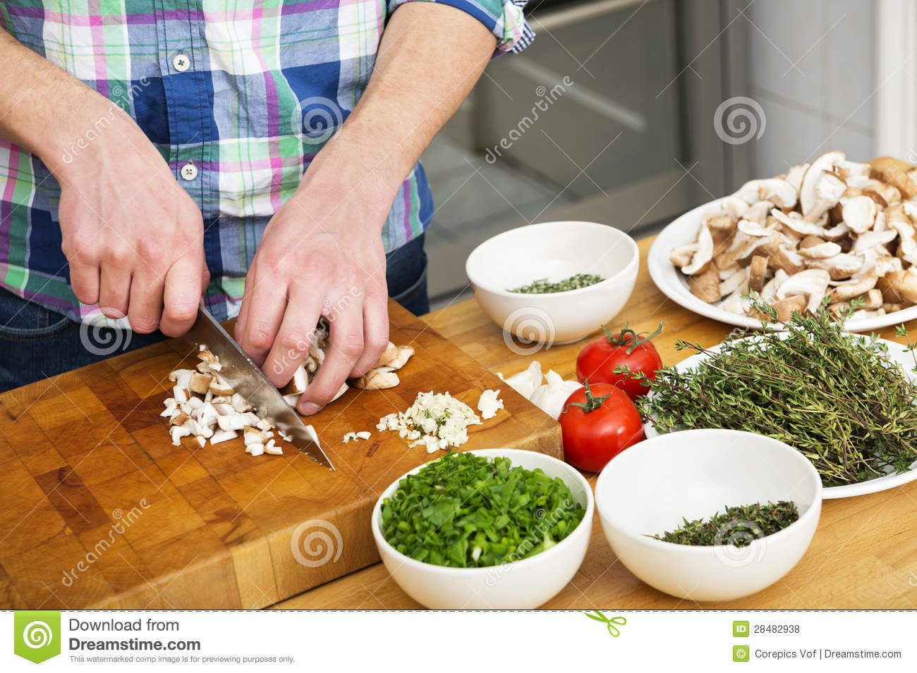 Man Chopping Mushrooms With Vegetables On Counter