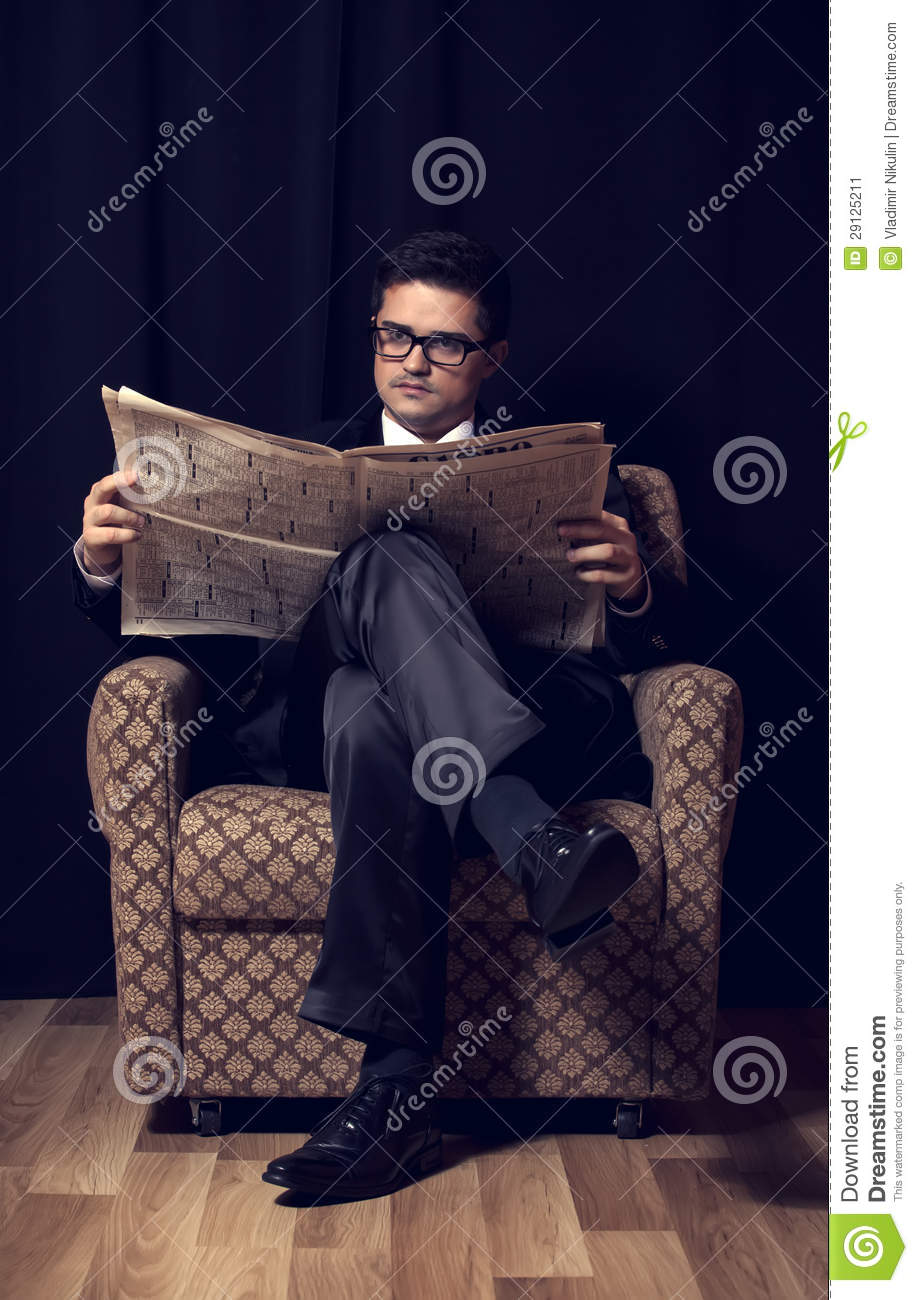 Man with cigarette and newspaper sitting in vintage for Sitting in armchair