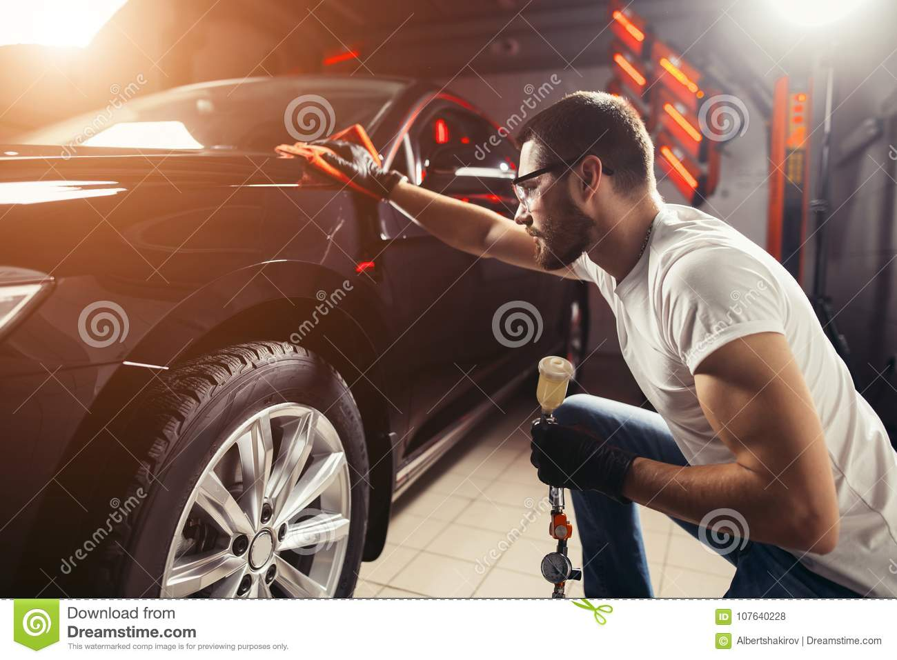 man cleaning car with microfiber cloth, car detailing or valeting