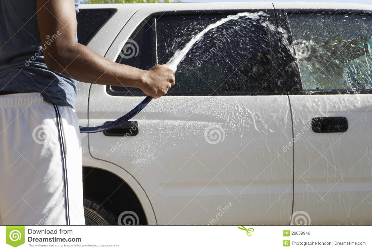 Man Cleaning Car With Water Hose Royalty Free Stock Image