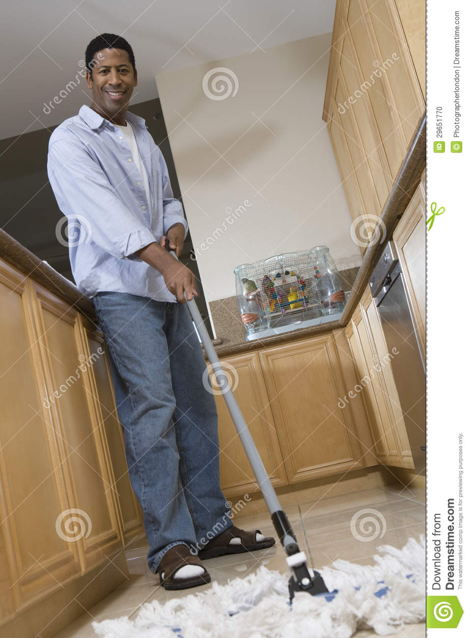 man cleaning the floor with mop stock photo