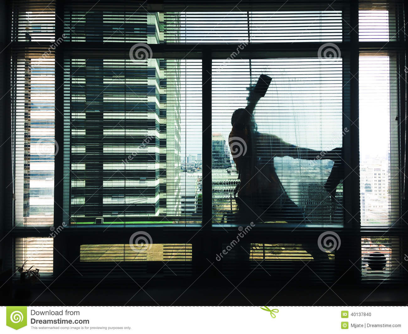 A man cleaning office building glass
