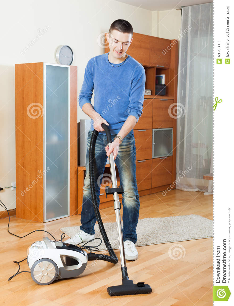 Man Cleaning With Vacuum Cleaner In Living Room Stock