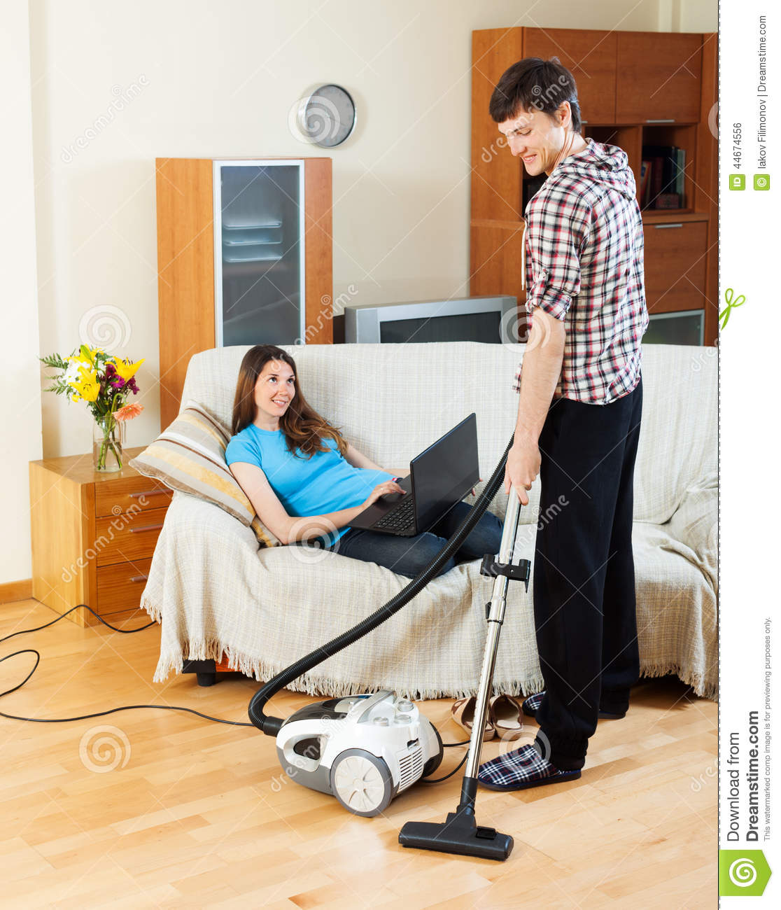 Man Cleaning While Woman Lying With Notebook Stock Photo