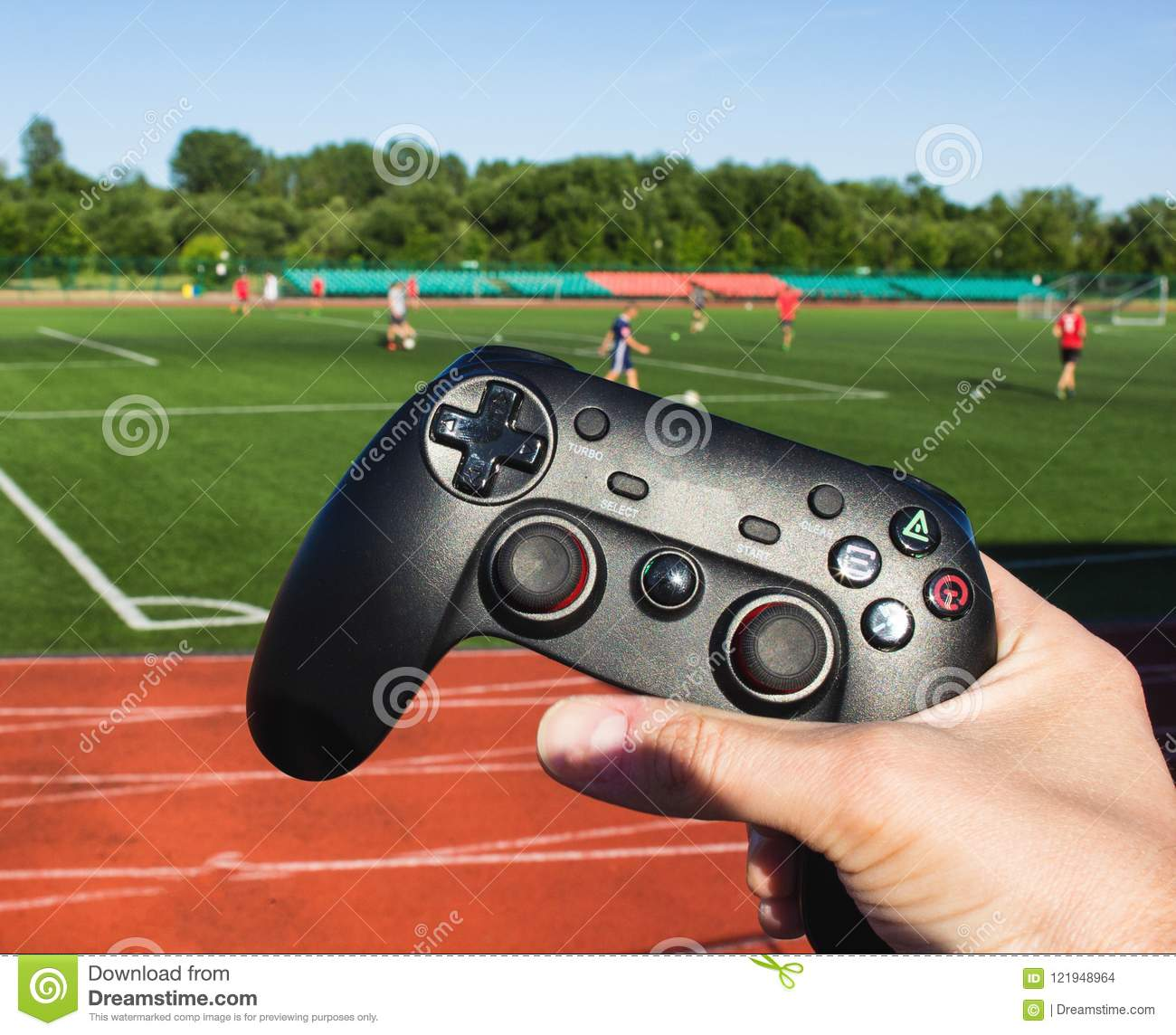 The man clicks on the buttons in the game joystick on the background of the stadium and the game of football, close-up