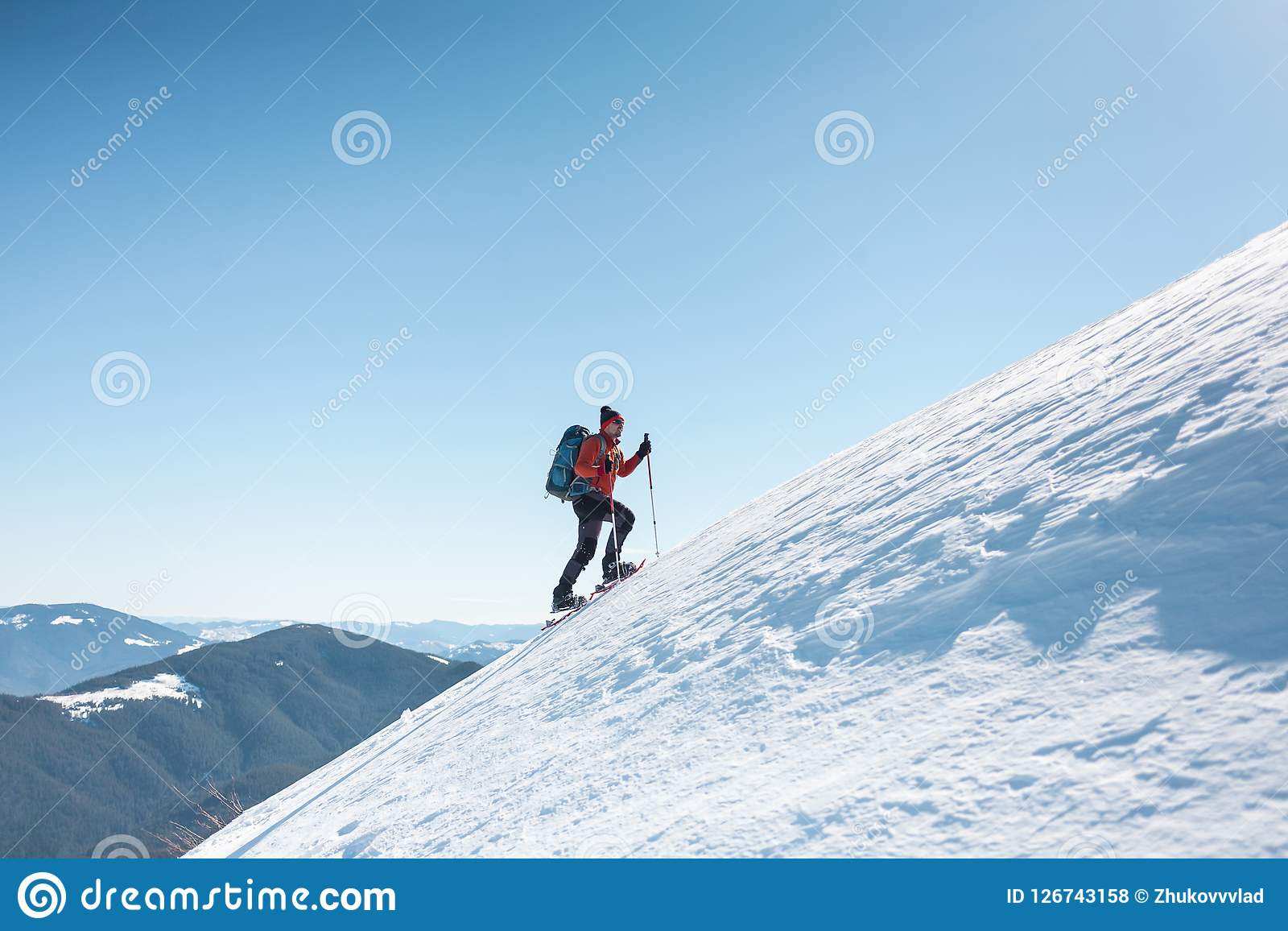 A man climbs to the top of the mountain.
