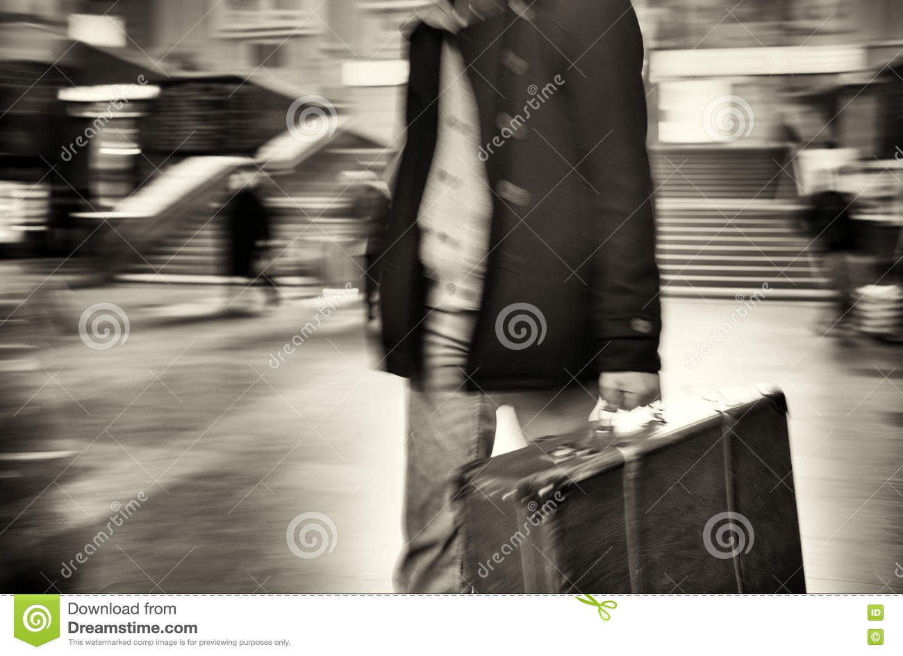 The man in the coat comes with a suitcase at the station blurred motion black and white photo