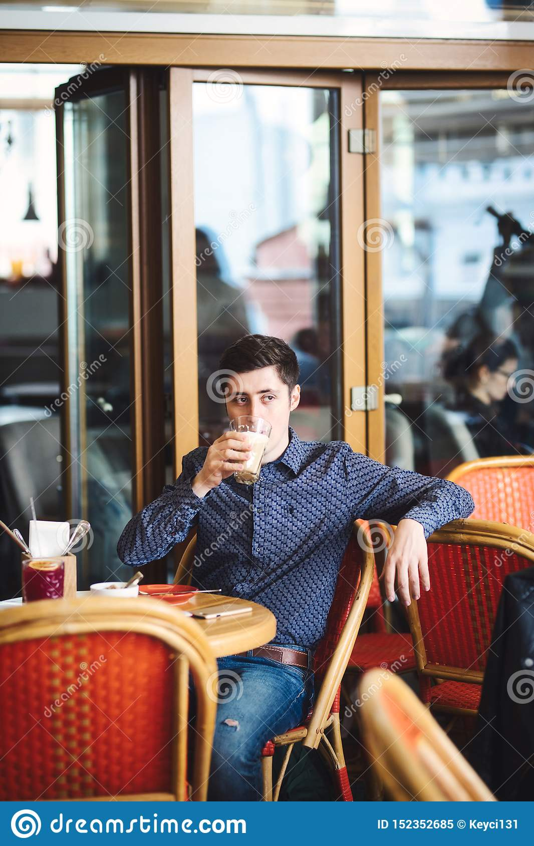Man drinking large latte at a cafe table