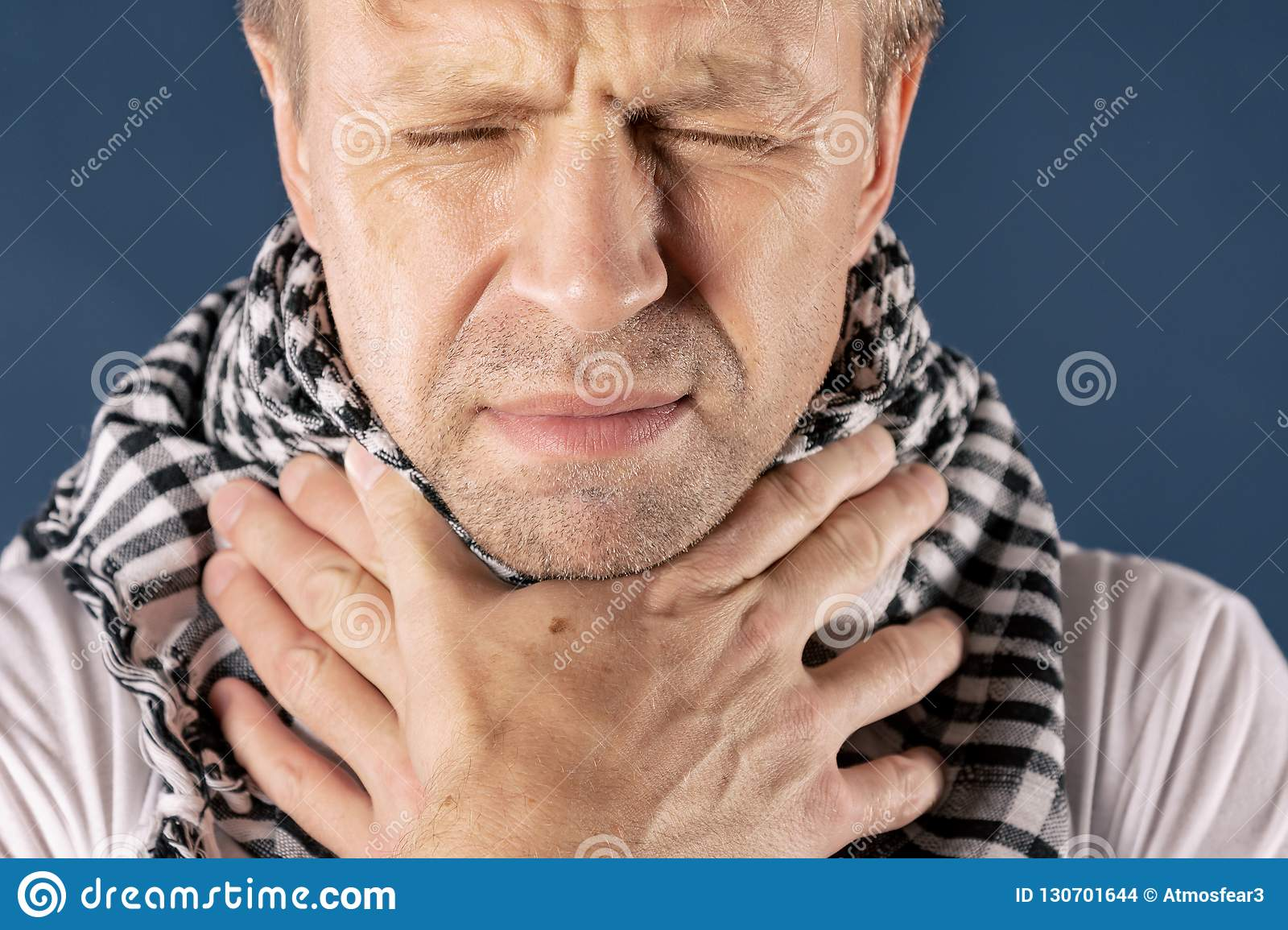Man with cold and flu illness suffering from sore throat. Blue background