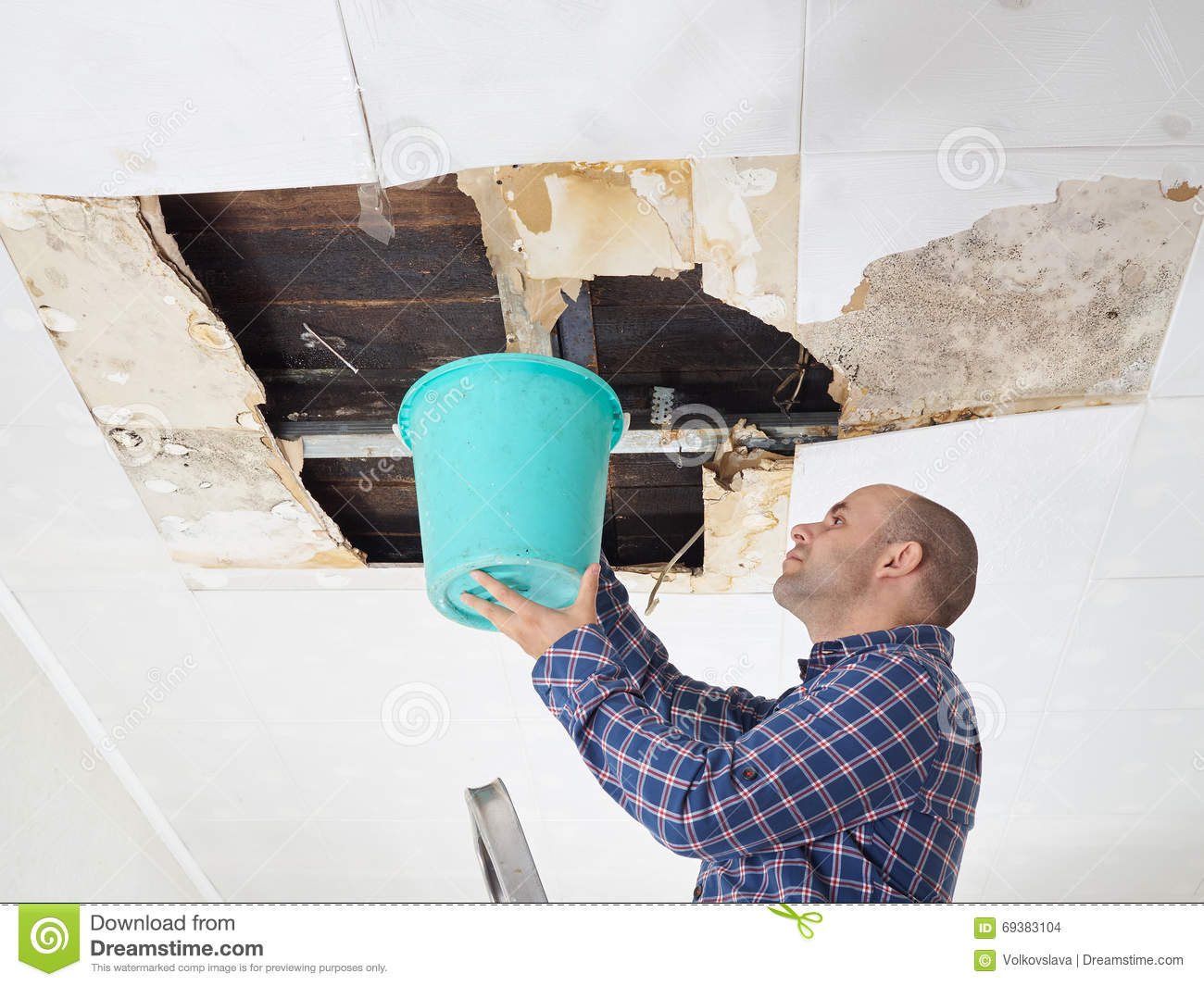 Man collecting water in bucket from ceiling stock photo - Water leakage from roof ...