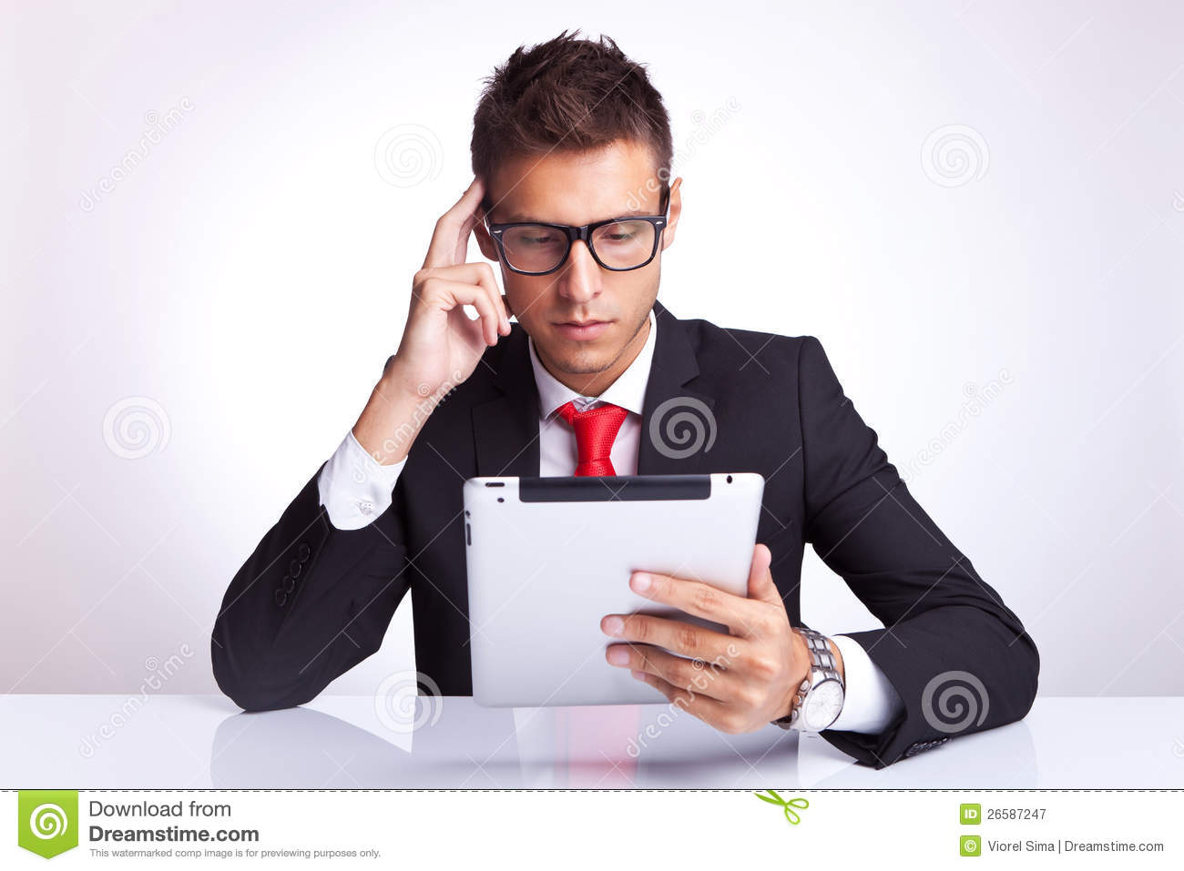 Man contemplating at what he is reading on pad