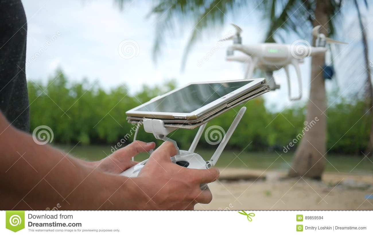 Man Controls Flying Quadcopter Via Remote Control With Tablet Gadget Screen Drone Pilot Practice Flight On The Beach Stock Footage