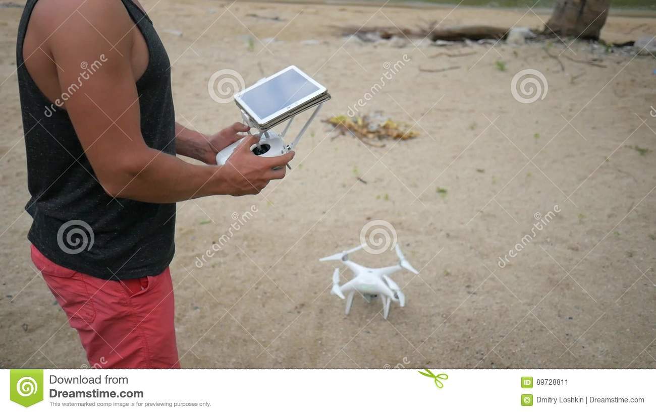 Man Controls Flying Quadcopter Via Remote Control With Tablet Gadget Screen Drone Take Off On The Beach HD Stock Video