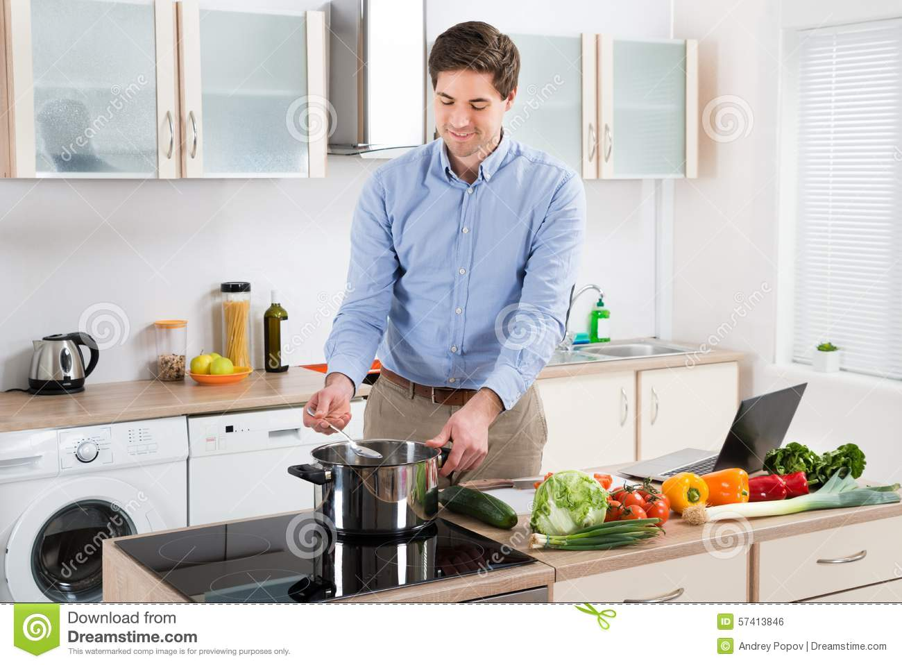 Man Cooking Food In Kitchen Stock Photo - Image: 57413846
