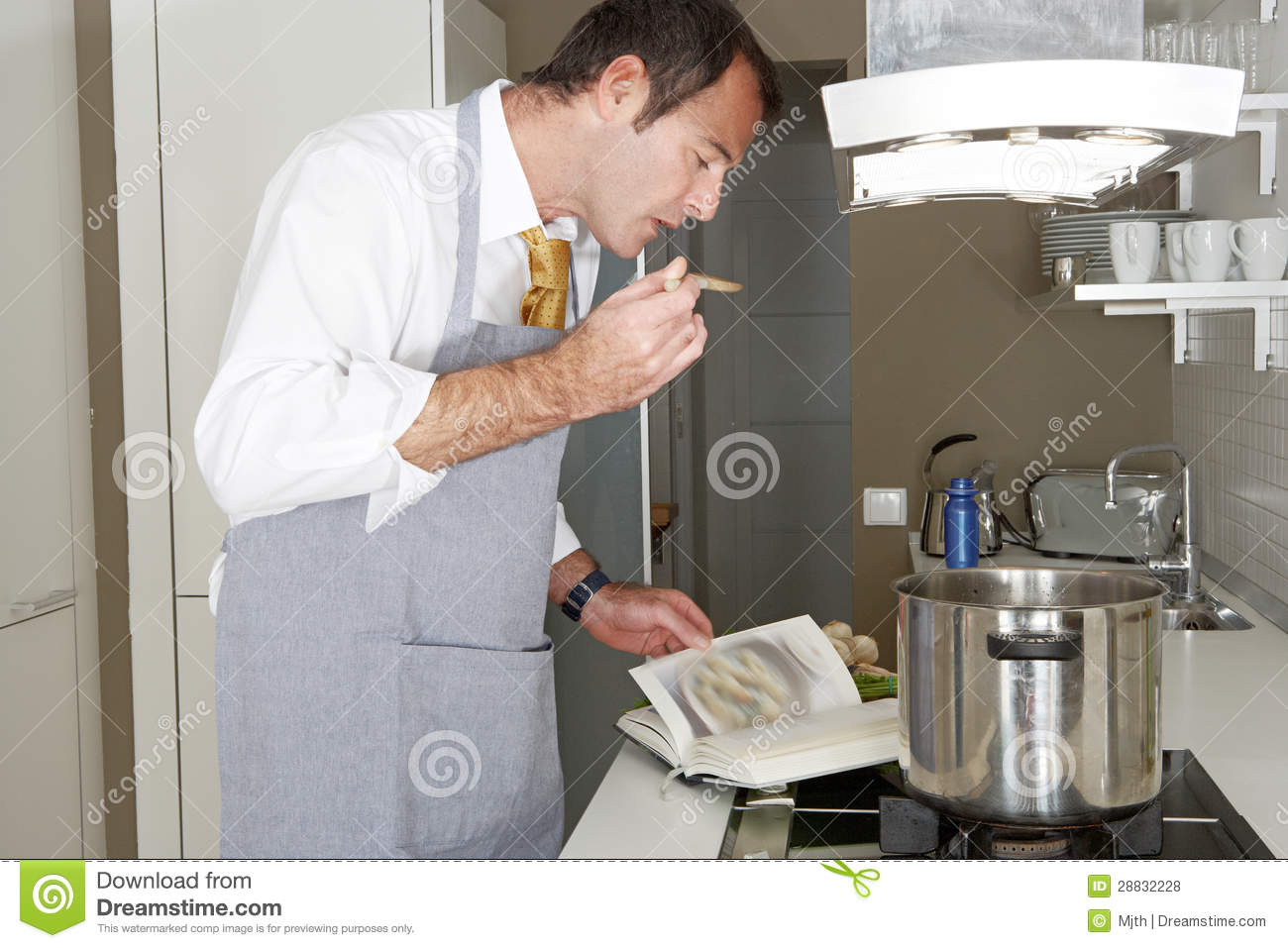 Male Chef Cook Reading Recipe Book While Preparing Food ...