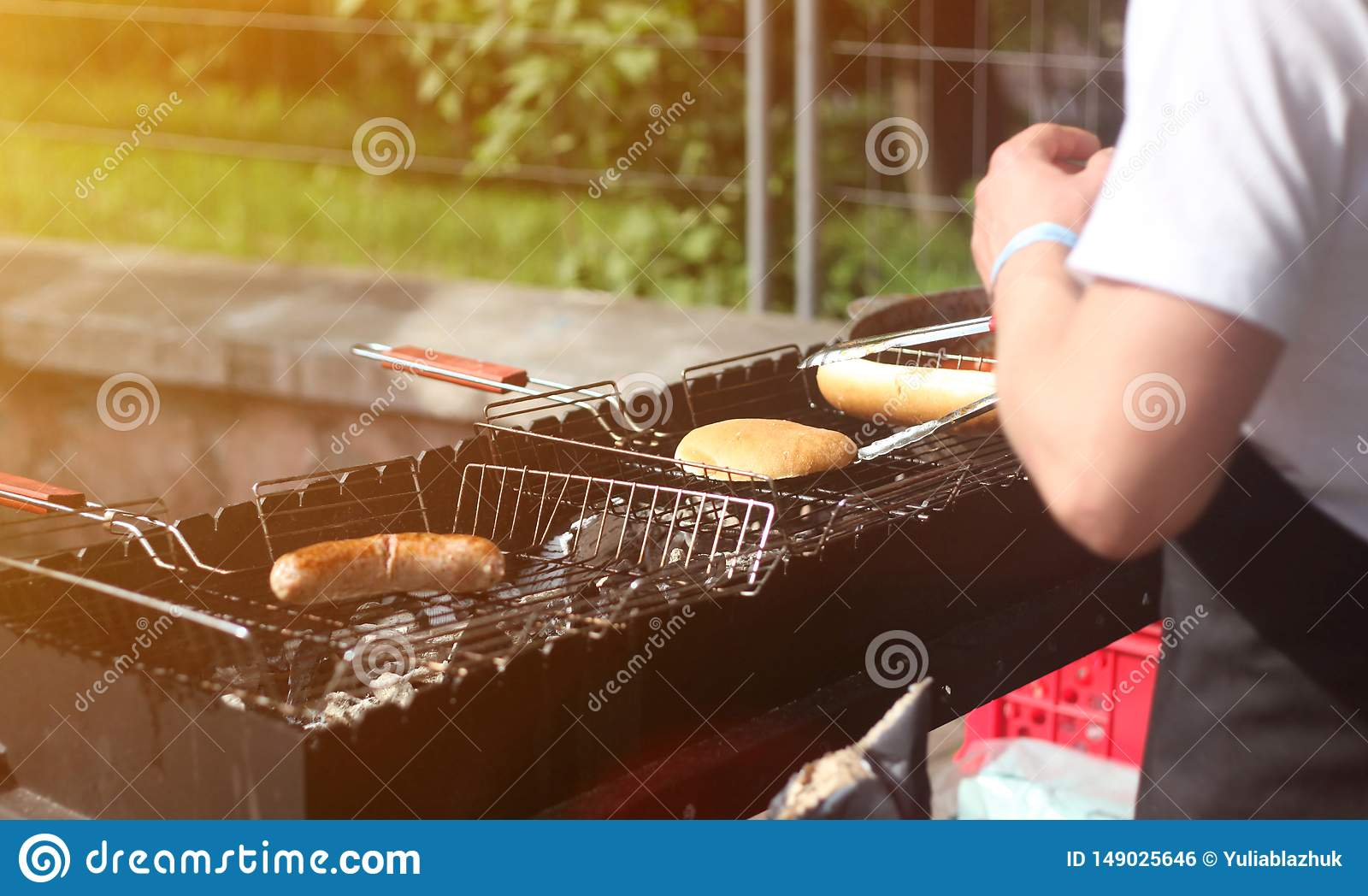 Man cooks sausages and buns for hot dogs and burgers on the grill outdoors