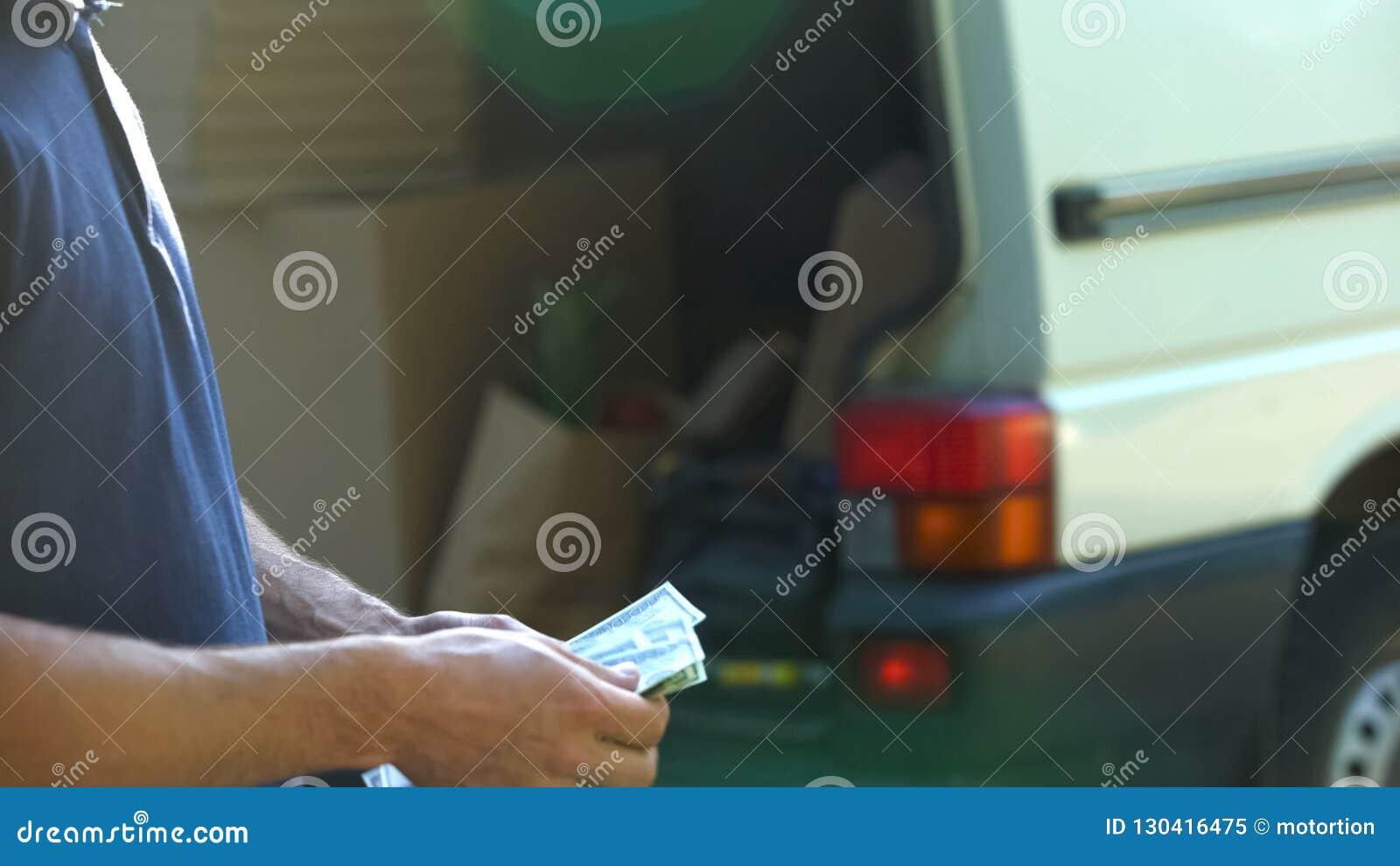 Man counting banknotes and closing van door, small business, moving company