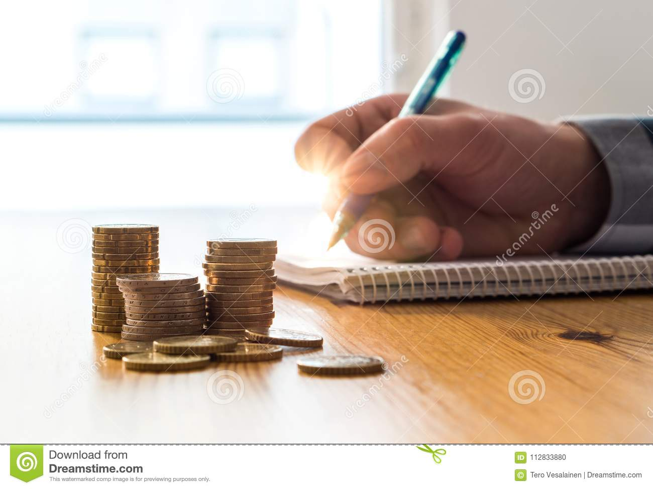 Man counting expenses, budget and savings and writing notes.