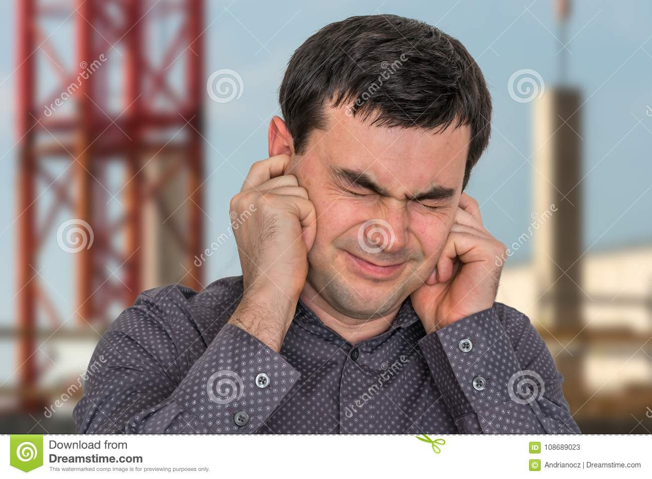 Man covering his ears to protect from loud noise