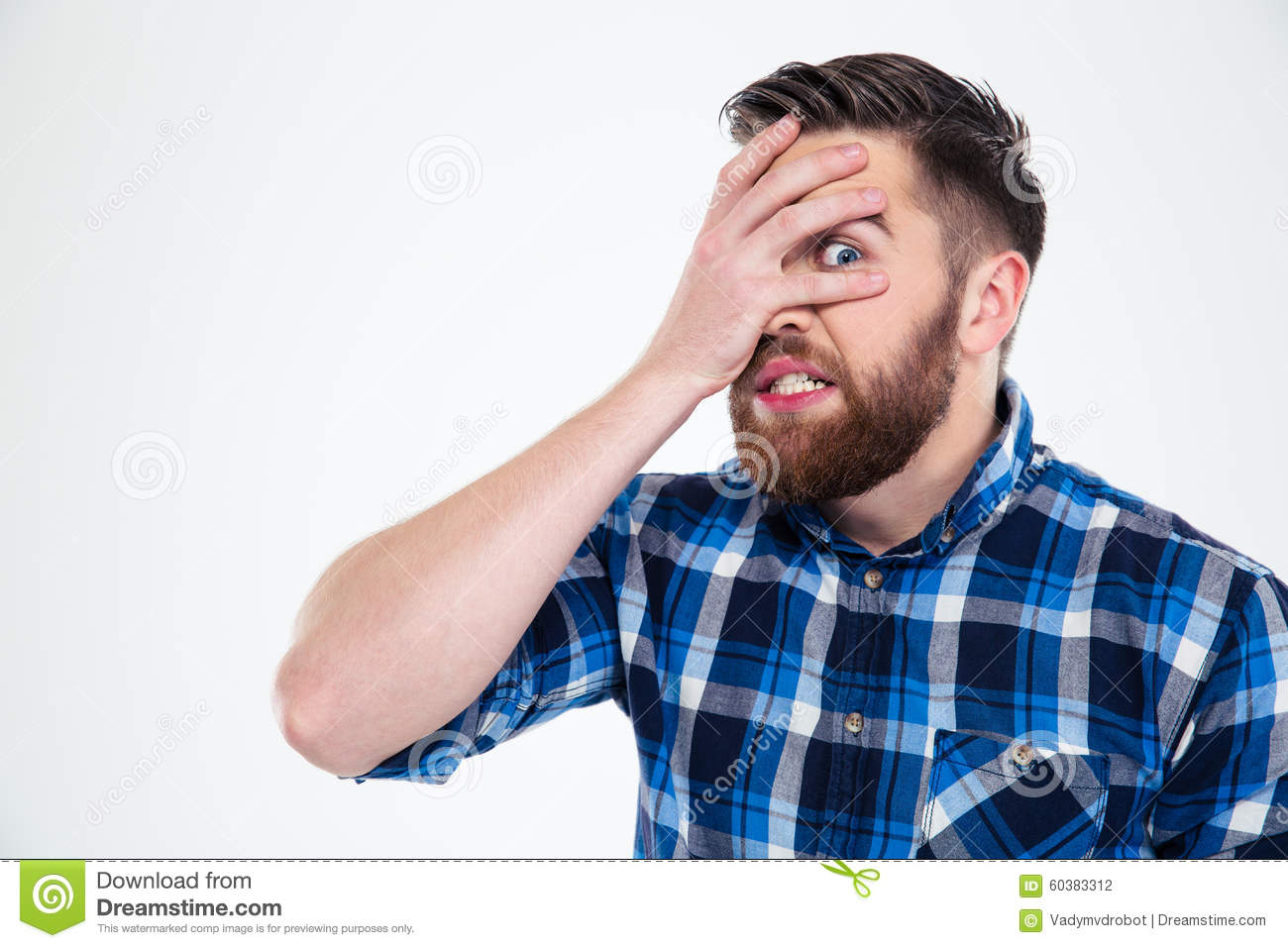 Man covering his face with palm and looking at camera through fingers