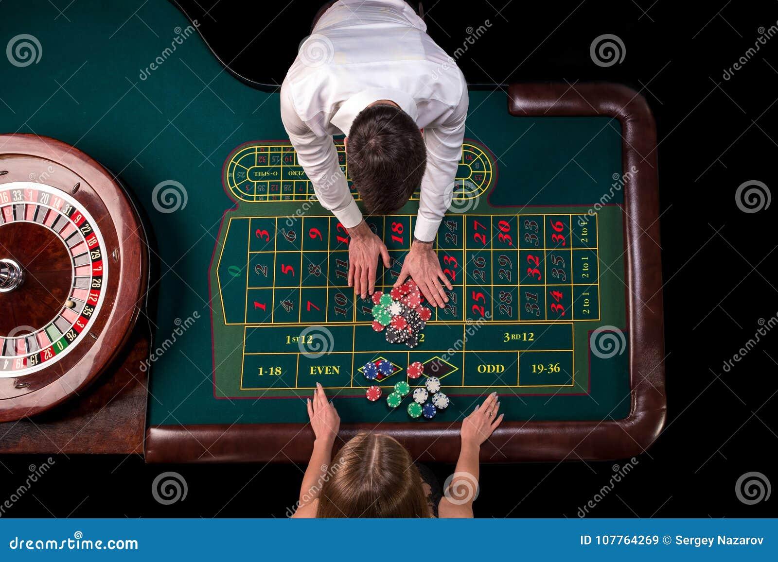 Man croupier och kvinnan som spelar rouletten på tabellen i kasinot Bästa sikt på en grön tabell för roulett med ett band