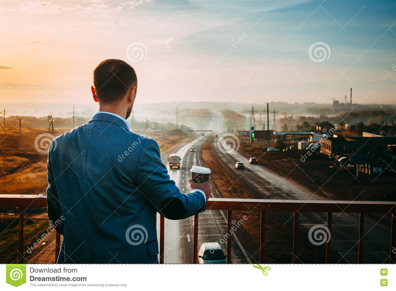 Man with Cup of coffee on the bridge. Early morning, the sunrise, the road disappears in the distance.