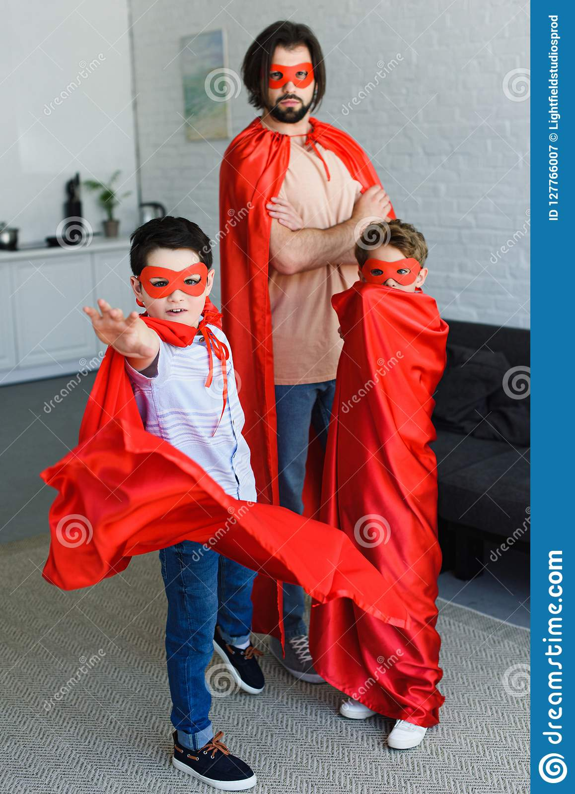 man and cute little sons in red superhero costumes