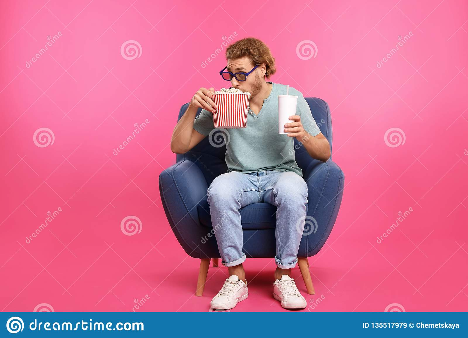 Man with 3D glasses, popcorn and beverage sitting in armchair during cinema show