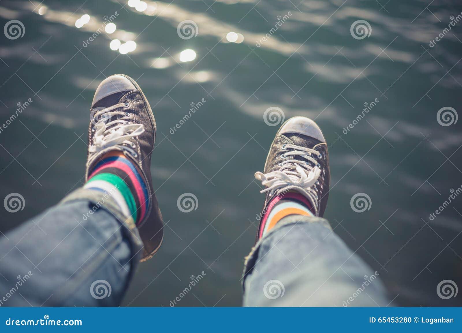 Man dangling feet over water