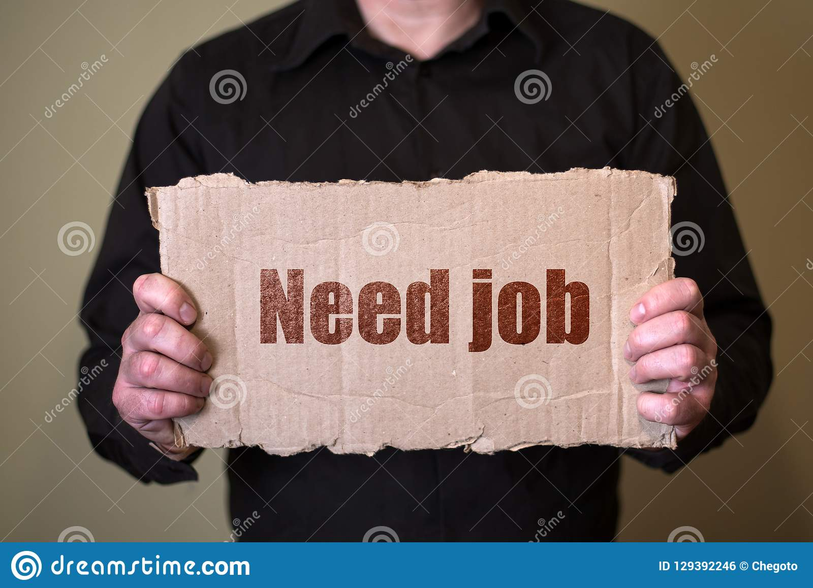 A man in a dark shirt holding a piece of cardboard with text Need Job